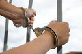 Handcuffed hands holding bars woman Royalty Free Stock Photography