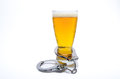 Handcuffs and beer glass around on isolated white represents alcoholism drunk driving or dui Royalty Free Stock Photos