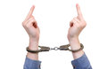 Handcuffs on hands closeup with middle finger gestutre isolated the white background Stock Image