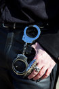 Handcuffs hanging on a belt of leather trouser man who is also wearing gothic rings Stock Photography