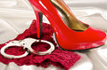Handcuffs and high heel close up on white background Stock Photography