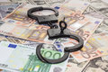 Handcuffs with key on background of euros and dollars Royalty Free Stock Photo