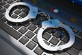 Handcuffs on laptop keyboard creative abstract cyber crime online piracy and internet web hacking concept macro view of metal Royalty Free Stock Photography