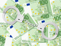 Handcuffs on one hundred euro background euros Stock Image