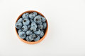 Handful of blueberries in wooden bowl isolated on white Royalty Free Stock Photo