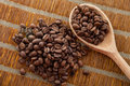Handful coffee beans and coffee beans in a wooden spoon Obrazy Royalty Free