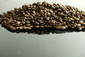 A handful of coffee beans on glossy black background Royalty Free Stock Images