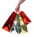 Handful of glossy shopping bags hand carrying red and gold shiny gift purchased from a mall Stock Photo