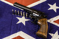 Handgun magnum and bullets on confederate battle flag Royalty Free Stock Image