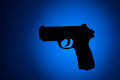 Handgun silhouette with blue and black background Stock Images