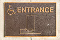 Handicap entrance sign made from rough textured metal on wall Stock Photos