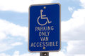 Handicap parking sign with sky background