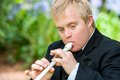 Handicapped boy playing block flute close up portrait of disabled young man outdoors Royalty Free Stock Photo