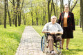 Handicapped elderly man with his wife men one leg amputated above the knee sitting in wheelchair in a wooded park standing at Royalty Free Stock Photos