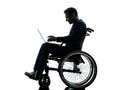 Handicapped man computing laptop computer in wheelchair silhoue one silhouette studio on white background Royalty Free Stock Photo