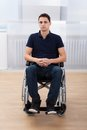 Handicapped man sitting on wheelchair at home full length portrait of young Royalty Free Stock Images