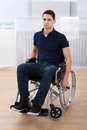 Handicapped man sitting on wheelchair at home full length portrait of young Stock Photography