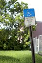 Handicapped parking sign rusty and crooked single that is blue wheelchair stencil on top the words by disabled permit Royalty Free Stock Photography