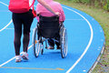 Handicapped person on a wheelchair with an aide on the athletic track during sporting event Royalty Free Stock Photos