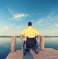 Handicapped young man in a wheelchair watching the sea in summer Stock Photo