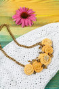 Handicraft necklace lies on the white lace dress background Royalty Free Stock Photo
