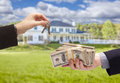 Handing Over Cash For House Keys in Front of Home Royalty Free Stock Photo