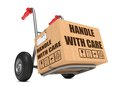 Handle with care cardboard box on hand truck slogan isolated white background Stock Photography