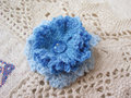 Handmade brooch blue flower on ecru crochet background Royalty Free Stock Photos