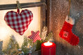 Handmade christmas wooden window decoration with heart and a red santa boot candle Stock Photos