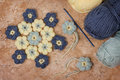 Handmade colorful crochet flower with skein on marble table selective focus Stock Photography