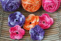 Handmade colorful crochet flowers with skein on wooden table selective focus Stock Image