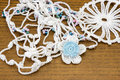 Handmade crochet white chain and a blue flower. Homemade necklace, needlecraft. Royalty Free Stock Photo
