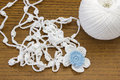 Handmade crochet white chain and a blue flower. Yarn ball for crochet or knitting on wooden table. Homemade necklace. Royalty Free Stock Photo