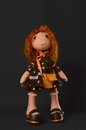 Handmade doll against a dark background has red hair and a beautiful dress Royalty Free Stock Photo