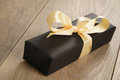 Handmade gift black paper box with yellow ribbon bow on wood table Royalty Free Stock Photo