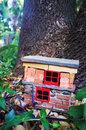 Handmade gnome house hand built garden decoration of a for gnomes and fairies against a large tree between ferns rocks and leaves Stock Image