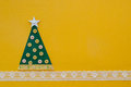 Handmade green christmas tree on yellow background copy space for your text Stock Photos
