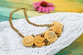 Handmade peach-colored necklace on a chain on the background of a lace dress Royalty Free Stock Photo
