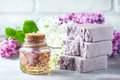 Handmade soap, Glass jar with fragrant oil and lilac flowers for spa and aromatherapy. Royalty Free Stock Photo