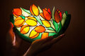 Handmade stained glass lamp with flowers tulips in woman s hands Royalty Free Stock Image