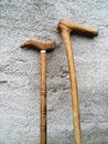 stock image of  Handmade wooden walking canes standing on the wall.