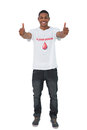 Handosme man wearing blood donor giving thumbs up tshirt on white background Stock Images