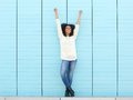 Hands in the air full length portrait of a cheerful young woman smiling with Royalty Free Stock Image