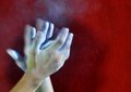 Hands with a ball of powder chalk magnesia against red Royalty Free Stock Photo