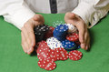 Hands betting casino chips in the foreground while Royalty Free Stock Images