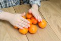 Hands of a boy with oranges wooden texture on human and Royalty Free Stock Photos