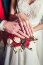 Hands bride and groom with rings on the bouquet closeup Royalty Free Stock Photo