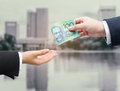 Hands of businessman passing Australian dollar (AUD) banknote. Royalty Free Stock Photo