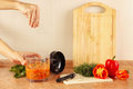 Hands of chef salt cooked vegetable mix in blender Royalty Free Stock Photo