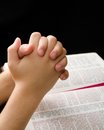 Hands of a child clasped in prayer praying with devotion over an open bible Stock Photos